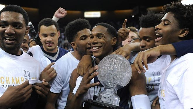 Marqueze Coleman, holding the trophy, was picked in Sunday's D-League draft.