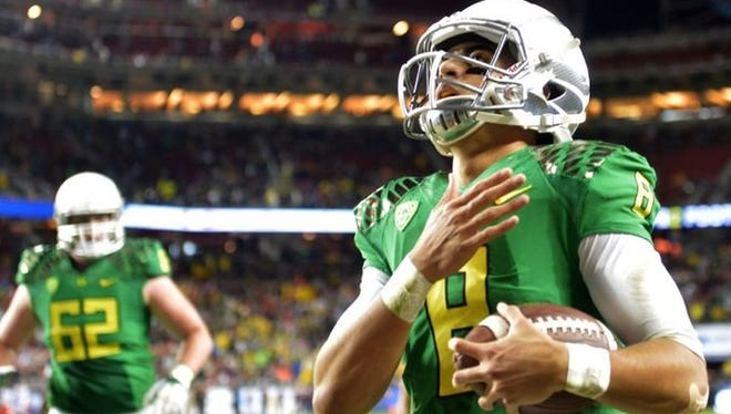 Oregon Ducks quarterback Marcus Mariota (8) celebrates after scoring on a 7-yard touchdown run in the second quarter against the Arizona Wildcats in the Pac-12 Championship at Levi's Stadium.