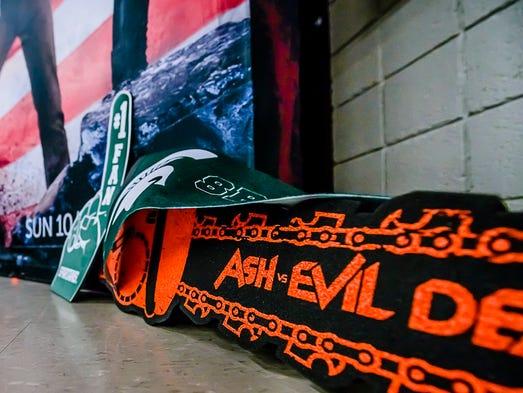 An 'Ash vs Evil Dead' foam chainsaw sits near MSU gear