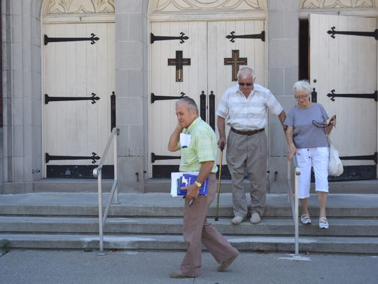 From left to right: Mike Haberstock, William Sagan, and Valeria Sagan walk out of the final mass held at St. Joseph's Church. The Sagans have been going to St. Joseph's for nearly 50 years.