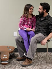 Logan Dyer sits down with his daughter Ella, 8, after conducting a free group guitar class for beginners at the North Park branch of the Evansville Vanderburgh Public Library in Evansville recently.  Dyer has offered several free group guitar classes and has loaned out instruments to those who do not have one for the classes.