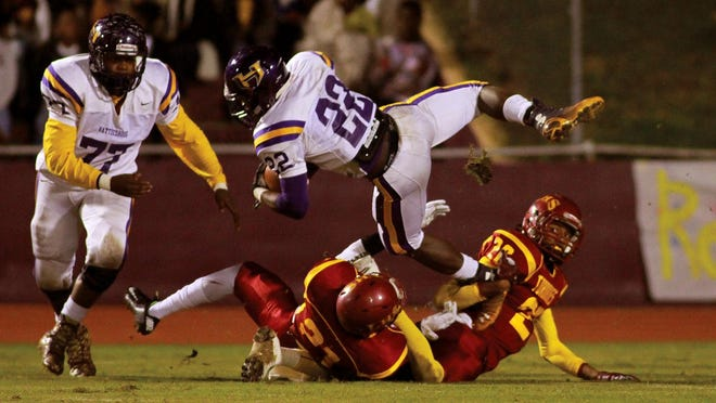 Hattiesburg running back Fabian Franklin dives for a few extra yards over Laurel defenders Shiwon Lovett (20) and Daveon Rogers (21) during playoff action Friday at Laurel.