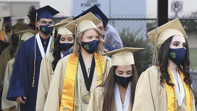 Members of the Class of 2020, all wearing face masks, file into a stadium at Yuma Catholic High School for the graduation ceremony Wednesday, June 10, 2020, in Yuma, Ariz., during the coronavirus pandemic.