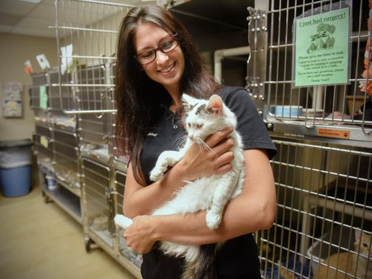 Rebecca Cartwright holds a cat available for adoption