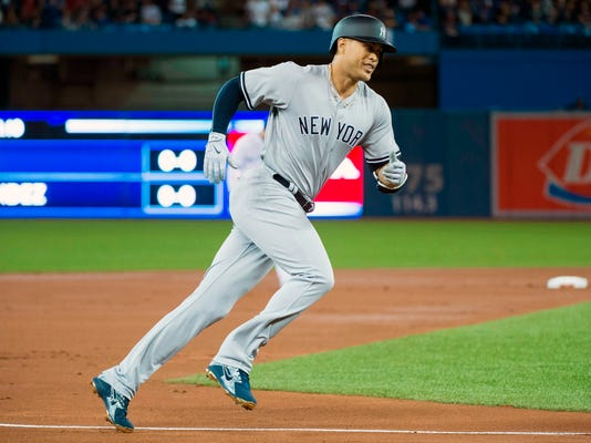 New York Yankees' Giancarlo Stanton rounds the bases after hitting a two-run home run during first-inning baseball game action against the Toronto Blue Jays in Toronto on Thursday, March 29, 2018. THE CANADIAN PRESS/Nathan Denette/The Canadian Press via AP)