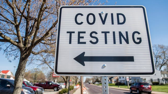 Signs direct vehicles into the Heartland Health Services parking lot for drive-through COVID-19 testing Tuesday, April 21, 2020 at 2321 N. Wisconsin Avenue in Peoria.