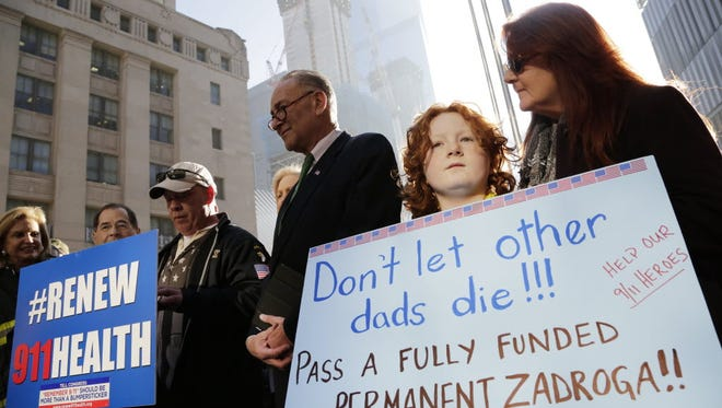Jack McNamara, 9, second from right, holds a sign on behalf of his late father during a rally in New York on Dec. 6, 2015, calling for renewal of the James Zadroga 9/11 Health and Compensation Act . John McNamara, who served in the New York Fire Department, worked at the World Trade Center site following the attacks of Sept. 11, 2001, and died in 2009 of cancer.