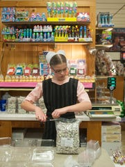 An Amish girl packs candy recently at the Amish Market