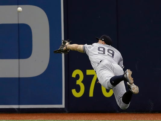 New York Yankees right fielder Aaron Judge (99) makes a diving catch on a fly-out by Tampa Bay Rays' Evan Longoria during the sixth inning of a baseball game Sunday, May 21, 2017, in St. Petersburg, Fla. Judge turned a double play against Rays' Corey Dickerson. (AP Photo/Chris O'Meara)