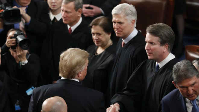 President Donald Trump shakes hands with Supreme Court Justice Brett Kavanaugh, after delivering his State of the Union address to a joint session of Congress on Feb. 5, 2019. Watching are from left, Supreme Court Chief Justice John Roberts, Associate Justice Elena Kagan and Associate Justice Neil Gorsuch.