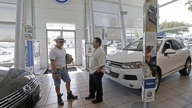 Customer Armando Barillas, left, talks to Sergio Rosas, sales manager at the New Century Volkswagen dealership in Glendale, Calif.