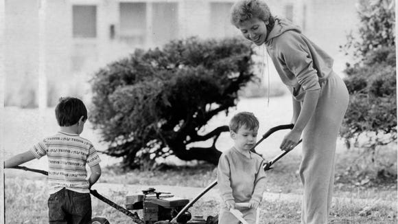 Lana Fite tries to keep up with the growing grass in her yard as her sons try to keep up with her in May of 1986. Fite is helped by Robbie, 3, and Adam, 21-months old.
