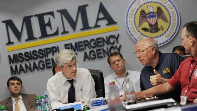 While in a conference in the Governor's Conference Room at Mississippi Emergency Management Agency in Pearl, Gov. Phil Bryant, left of center, listens to MEMA Director Robert Latham, second from right, as they go over the disaster declaration process during a statewide hurricane response exercise. The process simulated a category 3, 120 MPH storm which followed the same path Hurricane Katrina took in 2005.