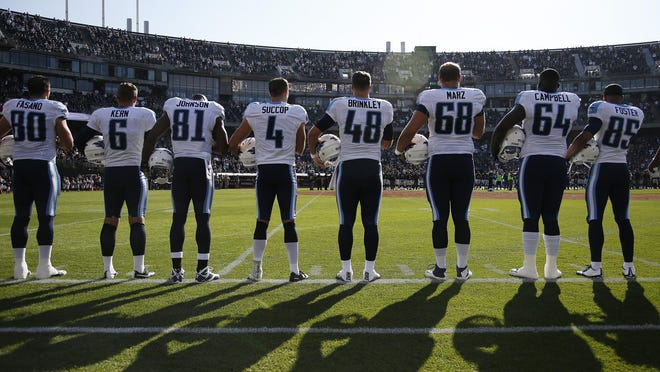 The Titans stand for the national anthem.