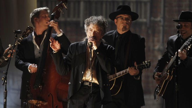 "In this Feb. 13, 2011 photo, Bob Dylan, center, performs at the 53rd annual Grammy Awards in Los Angeles. Dylan won the 2016 Nobel Prize in literature on Thursday, Oct. 13, 2016, a stunning announcement that for the first time bestowed the prestigious award on a musician for ""having created new poetic expressions within the great American song tradition."""