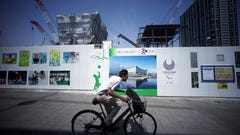 In this July 17, 2018, photo, a man rides a bicycle past Ariake Arena under construction during a media tour to the venue of the Tokyo 2020 Olympics in Tokyo. Volleyball and Paralympics' wheelchair basketball events will take place at the venue. (AP Photo/Eugene Hoshiko)