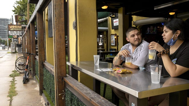 Jacob Ochoa and Amanda Garcia have drinks Wednesday at Little Woodrow's on West Sixth Street. The bar reopened after the Texas Alcoholic Beverage Commission voted last week to let bars count as food revenue sales from prepackaged food and food trucks. Gov. Greg Abbott had ordered bars, defined as establishments that derive more than half of their income from alcohol sales, to close amid a rise in coronavirus cases.