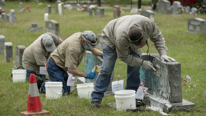 Austin Parks and Recreation Department employees, from left, Asension Alonzo, Ken Bloomer and Tommy Alexander remove paint from headstones at Evergreen Cemetery on Wednesday. More than a dozen headstones were defaced with blue paint Monday at the historic cemetery, the city's first major municipal graveyard for Black residents.