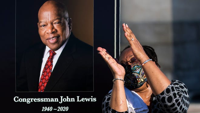 Jaquenette Ferguson from Oxon Hill, Md., gestures as she gets her picture taken beside a portrait of the late Rep. John Lewis, D-Ga., near the East Front Steps of the U.S. the Capitol, Tuesday, July 28, 2020, in Washington.