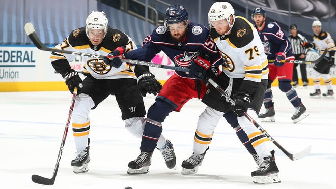 John Moore and Jeremy Lauzon (#79) of the Boston Bruins defend Emil Bemstrom of the Columbus Blue Jackets during the second period of an exhibition game prior to the 2020 NHL Stanley Cup Playoffs at Scotiabank Arena on July 30, 2020 in Toronto, Ontario.