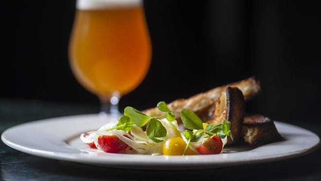 A salad featuring house-made mozzarella cheese with grilled Red Hen bread, shaved fennel, heirloom tomatoes, Pitchfork Farms pea shoots and nasturium paired with Hill Farmstead's Edward at Farmhouse Tap and Grill in Burlington on Wednesday, July 6, 2016.
