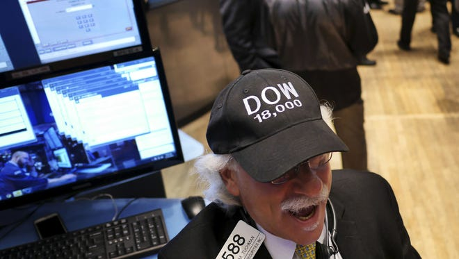 "Peter Tuchman wears a ""DOW 18,000"" hat on the floor at the New York Stock Exchange in New York, Tuesday, Dec. 23, 2014. The Dow passed 18,000 points for the first time."