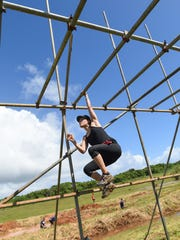 "The Score's Hannah Cho Iriarte displays her upper body strength in the ""Grease Monkey"" during the Konqer Obstacle Course Race at the Jose and Herminia Memorial Off-Road Park in Yigo on Nov. 29."