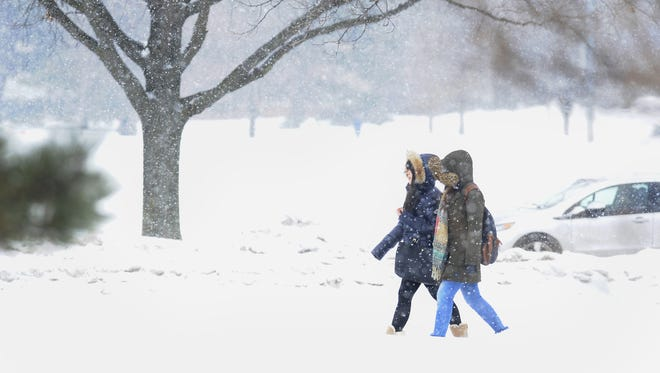 MSU students walk through the cold blowing snow and sleet on campus in East Lansing in March.