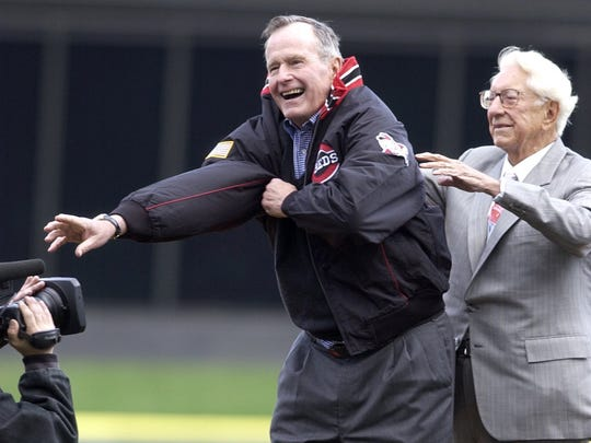 Reds owner Carl Lindner assists former President George Bush with a Reds jacket prior to throwing out the first pitch at Great American Ball Park in 2003.