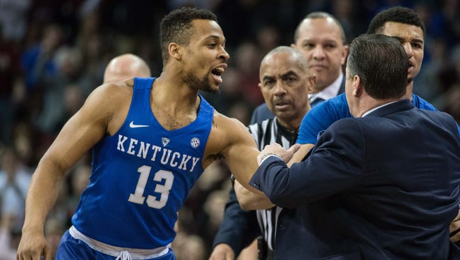 Kentucky guard Isaiah Briscoe (13) helps restrain head coach John Calipari as Calipari argued with the officials during the first half of an NCAA college basketball game against South Carolina, Saturday, Feb. 13, 2016, in Columbia, S.C.