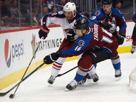 Columbus Blue Jackets center Boone Jenner, left, battles for control of the puck with Colorado Avalanche defenseman Nikita Zadorov, of Russia, right, and center Nathan MacKinnon in the second period of an NHL hockey game Thursday, Dec. 1, 2016, in Denver. (AP Photo/David Zalubowski)