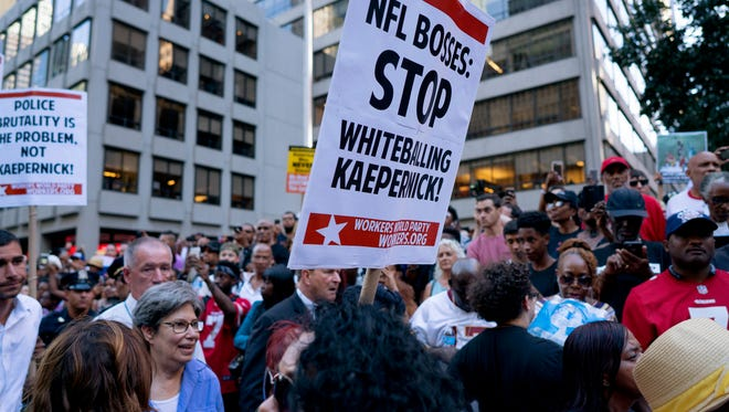 People gather in support of unsigned NFL quarterback Colin Kaepernick on Wednesday, Aug. 23, 2017, outside NFL headquarters in New York. (AP Photo/Craig Ruttle)