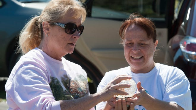 Tina Irby, right, locates a prized memento for her mother, Debra, left, during the cleanup of her mother's home Thursday morning. The Irby home was destroyed by Tuesday night's tornado.