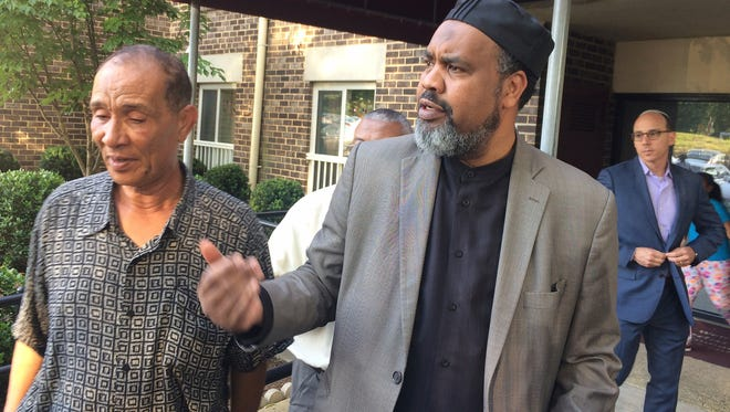 Mohmoud Hassanen Aboras, left, whose daughter Nabra Hassanen was killed, listens as Imam Mohamed Magid, center, of the All Dulles Area Muslim Society, talks about the case in Reston, Va.