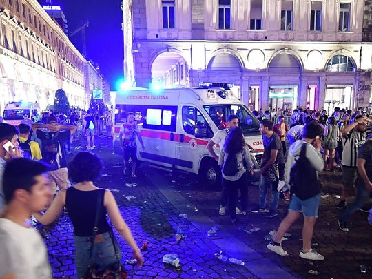 Juventus fan walk past an ambulance in San Carlo's square at the end of the Champions League final soccer match between Juventus and Real Madrid, in Turin, Italy, Saturday, June 3, 2017.  Juventus fans watching the Champions League final rushed out of a Turin piazza in panic Saturday after witnesses reported hearing a loud sound. (Alessandro Di Marco/ANSA via AP)