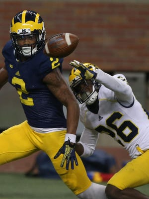 Michigan defensive back Jourdan Lewis defends Ahmir Mitchell during a practice held at Ford Field in Detroit on Saturday, March 26, 2016.