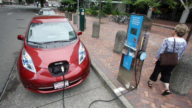 A Nissan Leaf charges at a electric vehicle charging station \ in Portland, Ore. Twenty-two built next year in the northwestern corner of the state.