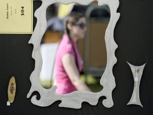 A woman walks past a piece made by Danny Sayre of Akron, OH as people attended the 40th annual Mt. Gretna Outdoor Art Show on Saturday, August 16, 2014.