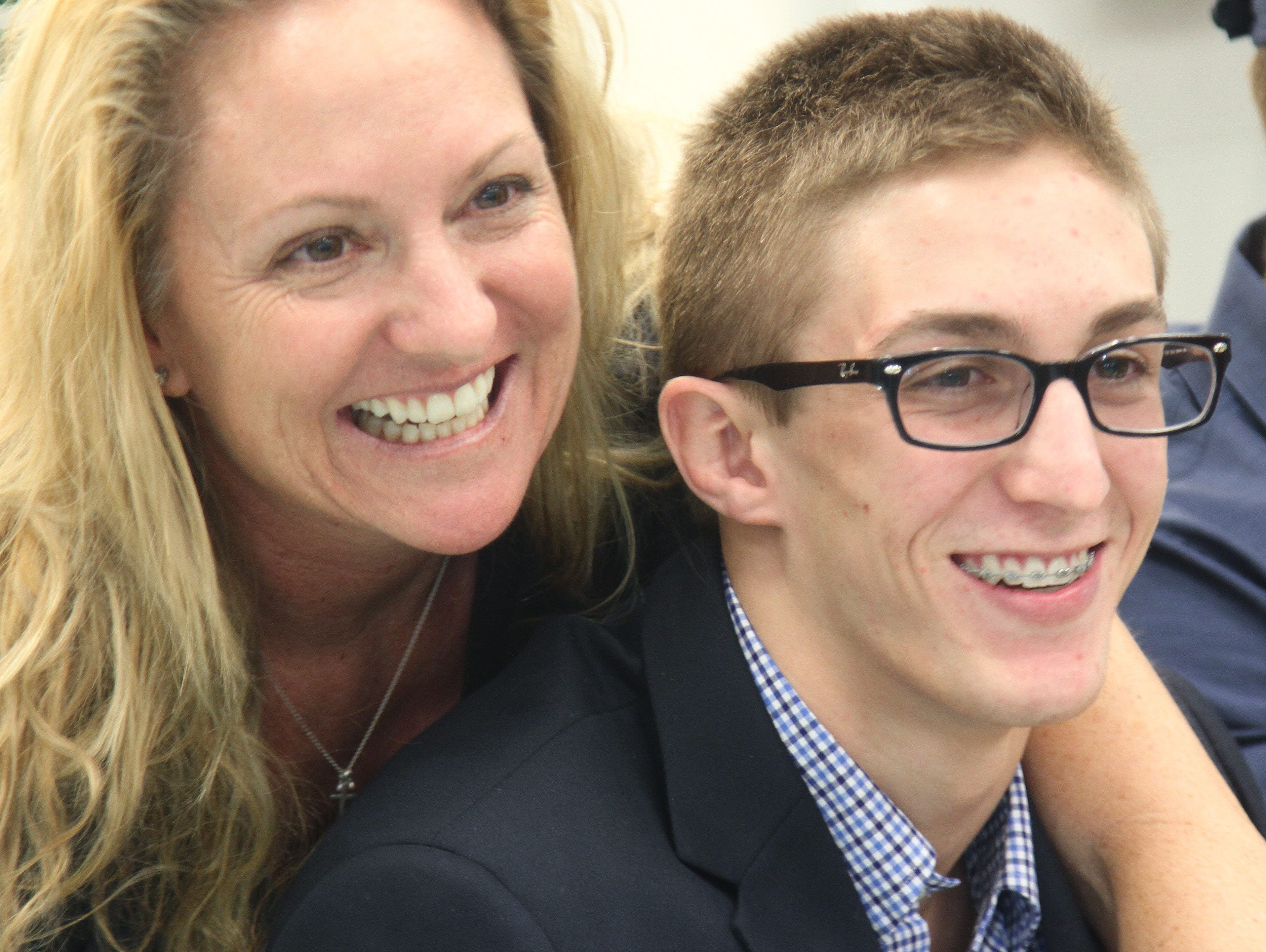 Colton Thomas, of Fort Myers High School, is congratulated by his mother, Jennifer Thomas, during National Signing Day on Wednesday.