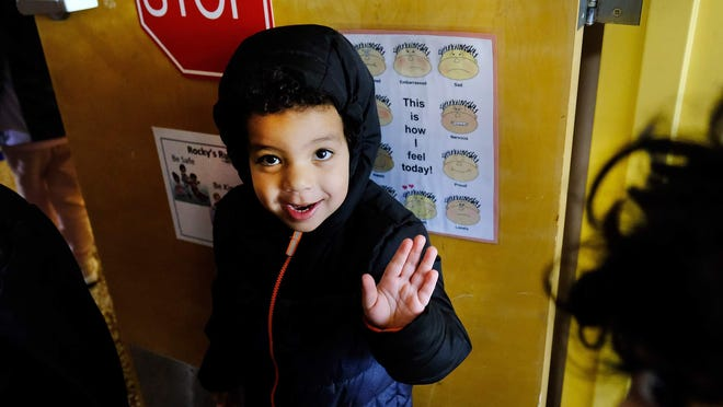A preschool student enrolled in a Head Start program in Portsmouth waves hello to a photographer before heading out to recess.