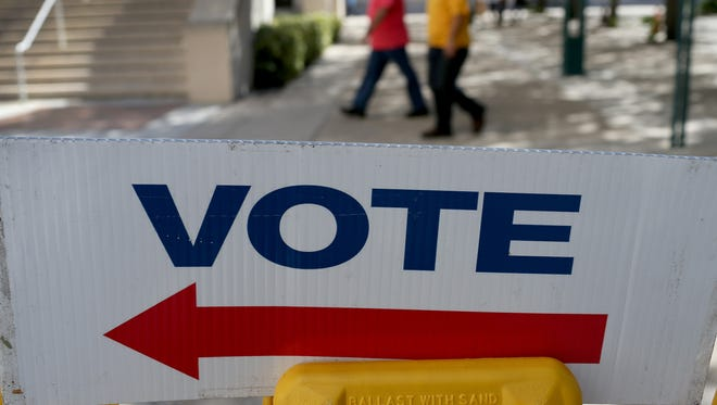 A sign points to the early voting station at a government building in Miami on Oct. 28, 2014.