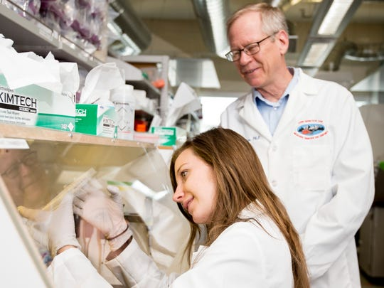 Paul S. Keim, Ph.D. Director, Regents Professor and the Cowden Endowed Chair of Microbiology, watches as student Cedar Mitchell works in a lab at NAU. She is working on DNA sequencing plague samples from Madagascar.