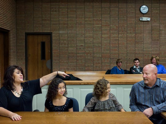 Michele Simpson smiles and points to E'Lena, 8, after E'Lena was too nervous to say her name aloud, while sitting with her sister Ceionna, 10, and Simpson's husband, Chad, during their adoption finalization hearing in front of Judge Elwood Brown on Friday, at the St. Clair County Courthouse in Port Huron.