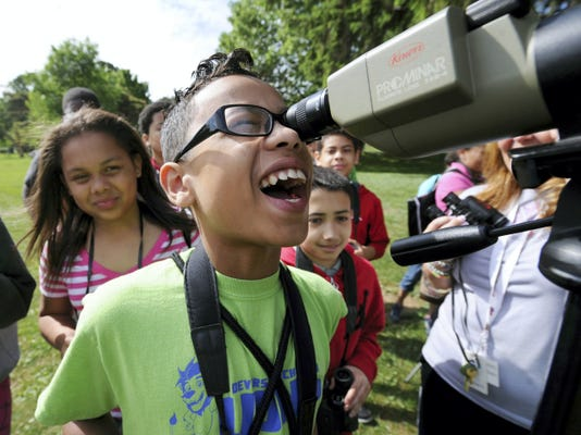 Abdias Hernandez, a Devers sixth-grader, reacts to looking through a telescope while bird watching and counting at Kiwanis Lake on Friday. The York Audubon Society teamed up with the class and set up four learning stations around the lake as well as planting new trees  for the herons and egrets.
