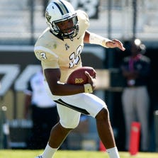 ORLANDO, FL - OCTOBER 26:  Justin Holman #13 of the UCF Knights runs for yardage during the game against the Connecticut Huskies at Bright House Networks Stadium on October 26, 2013 in Orlando, Florida.  (Photo by Sam Greenwood/Getty Images)