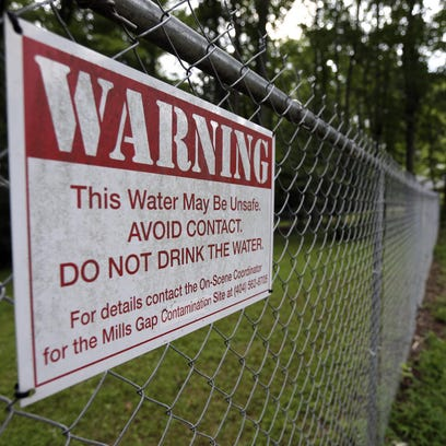 In this 2014 photo, a warning sign hangs on a fence surrounding a family's property near the former CTS plant in Asheville, now a Superfund Site.