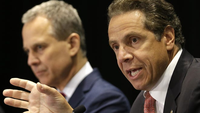 New York Governor Andrew Cuomo, right, speaks while New York Attorney General Eric Schneiderman listens during a news conference in New York, Wednesday, July 8, 2015. Cuomo has issued an executive order that puts the office of the state attorney general in charge of investigating killings by police. (AP Photo/Seth Wenig)