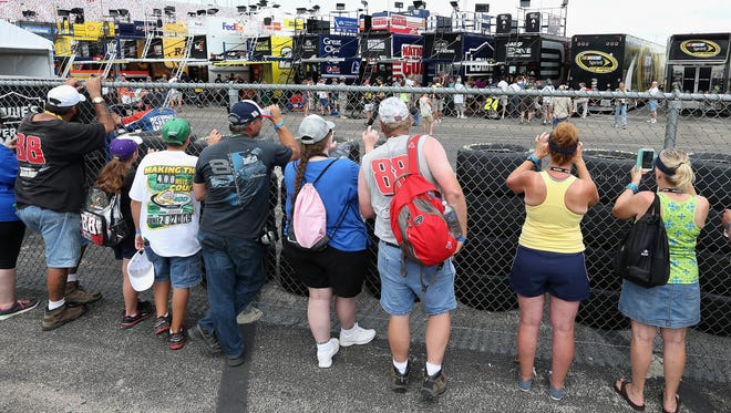 Fans watch for drivers and crew members through a chain-link fence surrounding the hauler area at Kentucky Speedway.