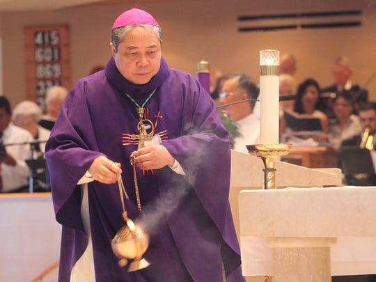 Archbishop Bernadito Auza uses a thurible as a symbolic offering to God during Mass at St. John XXIII Catholic Church on Sunday.