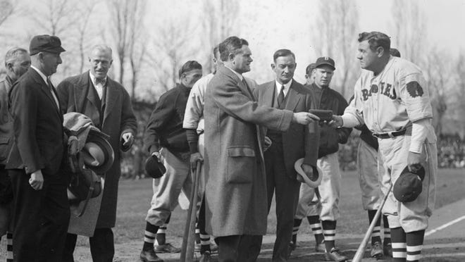 """Boston Braves slugger Babe Ruth is presented with the """"key to the city"""" from Worcester Mayor John Mahoney prior to an April 1935 preseason exhibition game between the Braves and Holy Cross."""